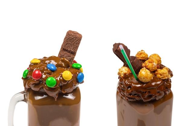 Шоколадный молочный коктейль со взбитыми сливками, печеньем, вафлями, подается в стеклянной стеклянной банке.