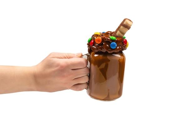 ガラスのメイソンジャーで提供されるホイップクリーム、クッキー、ワッフルとチョコレートミルクセーキ。 「女性の手で隔離。テキストやデザインのためのスペース。