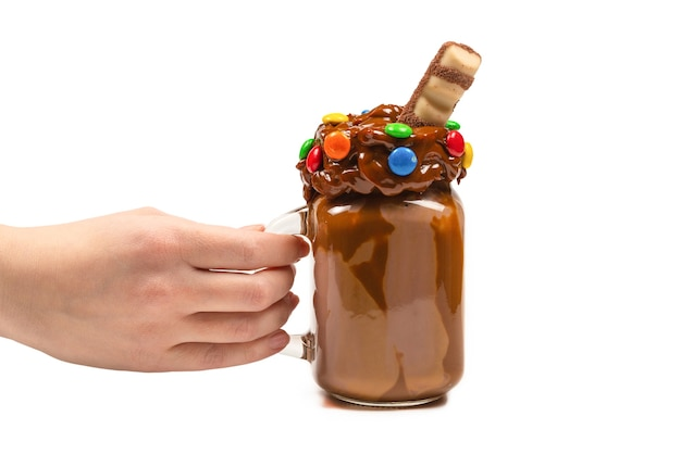 Шоколадный молочный коктейль со взбитыми сливками, печеньем, вафлями, подается в стеклянной стеклянной банке. «в руке женщины изолированы. место для текста или дизайна.