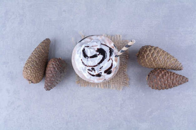 Chocolate milkshake with whipped cream and pine cone on marble table.