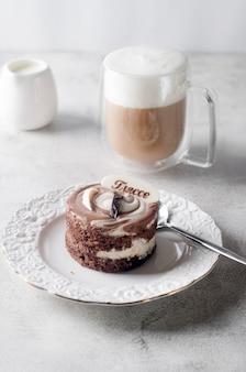 エレガントな白いプレートとカプチーノのチョコレートミニケーキ、ライトグレーの背景、上面図のガラスカップの泡。美味しいデザート。朝食のテーブルの場所の設定。