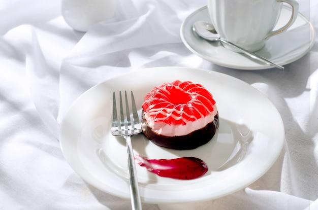 Шоколадный мини-торт с ягодным зефиром и желе в тарелке и чашкой кофе в стеклянной чашке на светло-сером фоне, вид сверху. вкусный десерт. сервировка стола для завтрака.