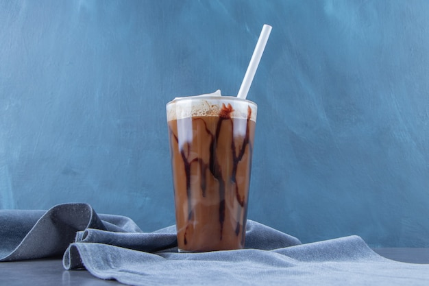 Chocolate mocha in a glass on piece of fabric , on the blue background.