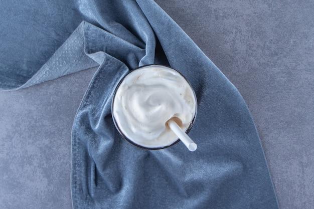 Шоколадный мокко в стакане на куске ткани, на синем столе.