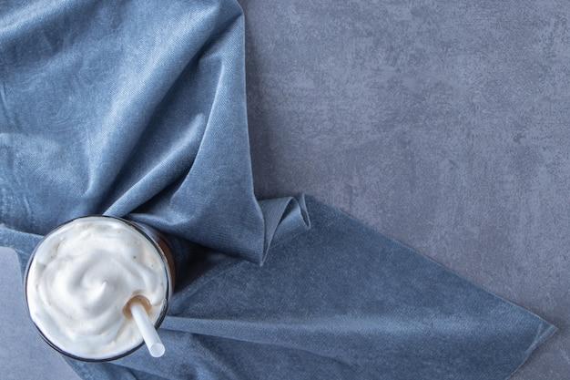 青いテーブルの上に、一枚の布の上にガラスのチョコレートモカ。