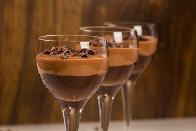 Chocolate mousse in a glasses on a wooden surface