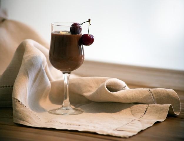 Шоколадный мусс-соус в стакане с вишней на деревянном столе вкусный чай латте в деревенском стиле