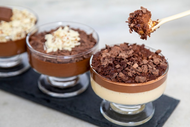 Chocolate mousse on spoon with white chocolate shavings.