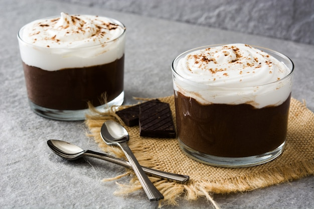 Chocolate mousse with cream in glass on gray
