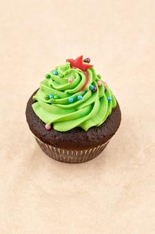 グリーンクリームとチョコレートマフィンケーキ。明るい背景、垂直フレームにクローズアップ