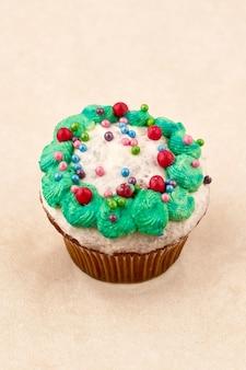 軽い釉薬とグリーンクリームが入ったチョコレートマフィンケーキ。明るい背景、垂直フレームにクローズアップ