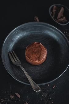 포크로 어두운 접시에 초콜릿 머핀 치즈 케이크
