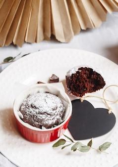 Шоколадный кекс в красной чашке. мокап валентина черное сердце copyspace. маленькая глазурованная керамическая формочка с коричневым пирогом на белом фоне.