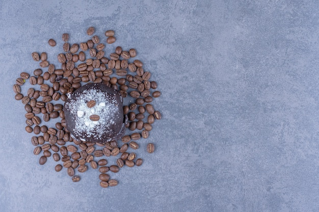 A chocolate muffin with coffee beans and sugar powder
