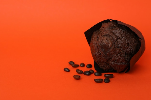 Chocolate muffin with coffee seeds on orange background.