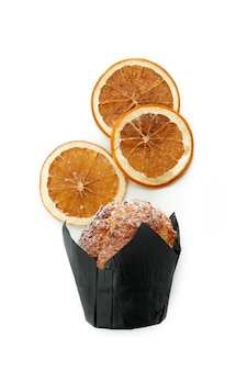 Chocolate muffin with orange slices isolated on white background.