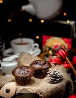 テーブルの上のチョコレートマフィンと松ぼっくり