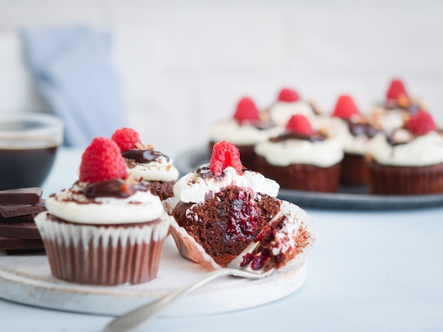 Chocolate muffins, cupcake cut in half with a cup of coffee and fresh raspberries on the table