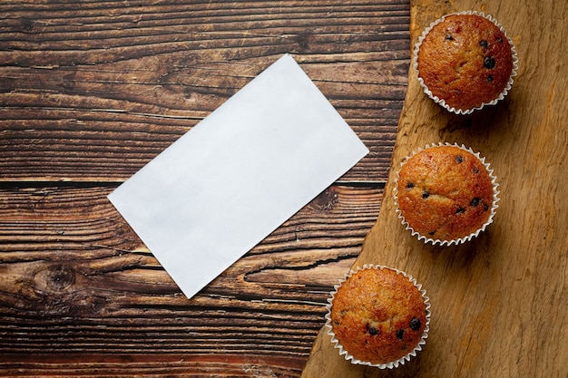 Chocolate muffins and empty white paper put on wooden floor