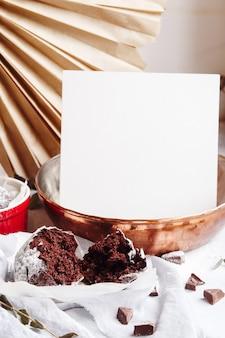 빨간 컵에 초콜릿 머핀입니다. 이랑 백서 copyspace입니다. 회색과 흰색 배경에 갈색 케이크가 있는 작은 유약 세라믹 라메킨.