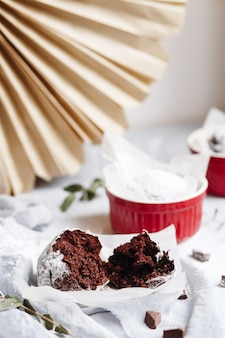 빨간 컵에 초콜릿 머핀입니다. 회색과 흰색 배경에 갈색 케이크가 있는 작은 유약 세라믹 라메킨.