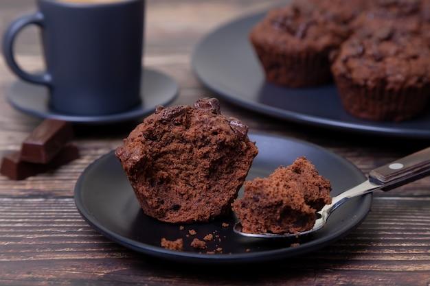 검정 잉크 판에 초콜릿 머핀입니다. 수제 베이킹. 배경에는 커피 한 잔과 머핀이 담긴 접시가 있습니다. 나무 배경입니다. 선택적 초점을 닫습니다.