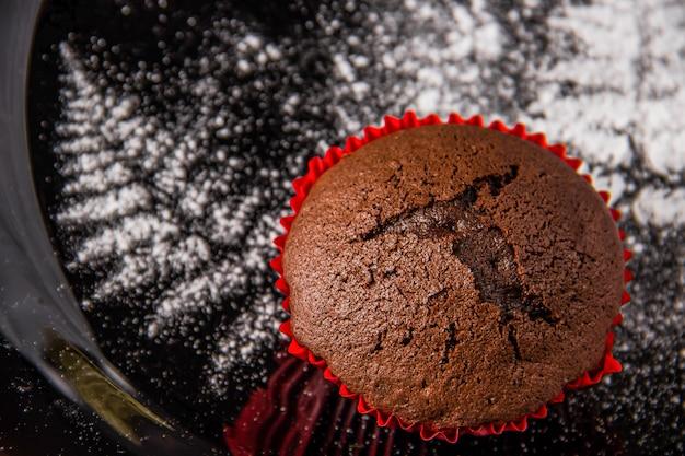 粉砂糖で描かれた小枝の装飾が施された暗い背景にチョコレートのマフィン