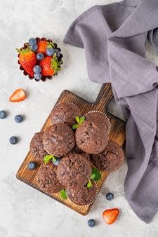 회색 배경의 나무 판자에 초콜릿 방울이 있는 초콜릿 머핀 또는 컵케이크