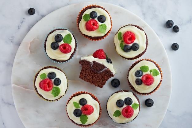 チョコレートマフィンまたはカップケーキ、ホイップクリームとベリー、フラットマーマー石の上に横たわっていた