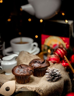 Chocolate muffins and pine cone on the table