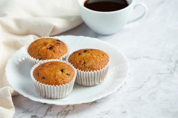 Muffin al cioccolato messi sul piatto bianco rotondo con una tazza di caffè
