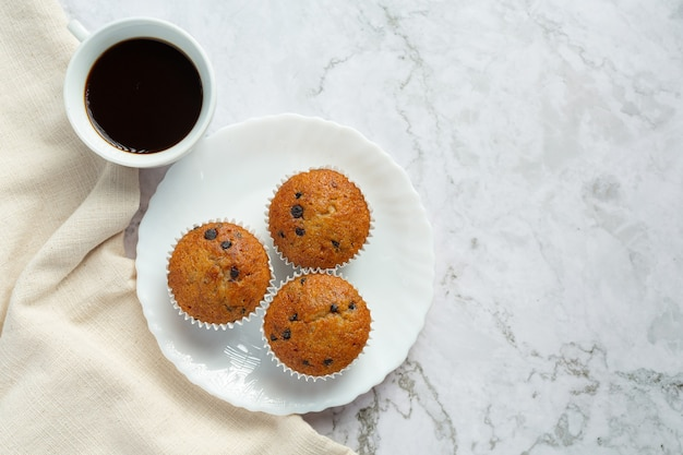Chocolate muffins put on round white plate with a cup of coffee