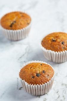 Muffin al cioccolato messi sul pavimento di marmo bianco