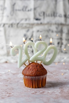 Chocolate muffins on top 2020 candles on light brown surface