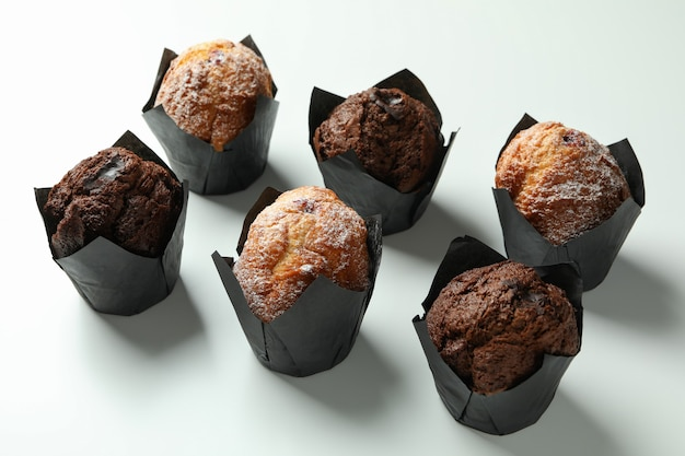 Chocolate muffins on white background, close up.