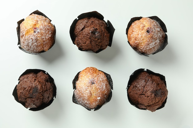 Chocolate muffins on white background, top view.