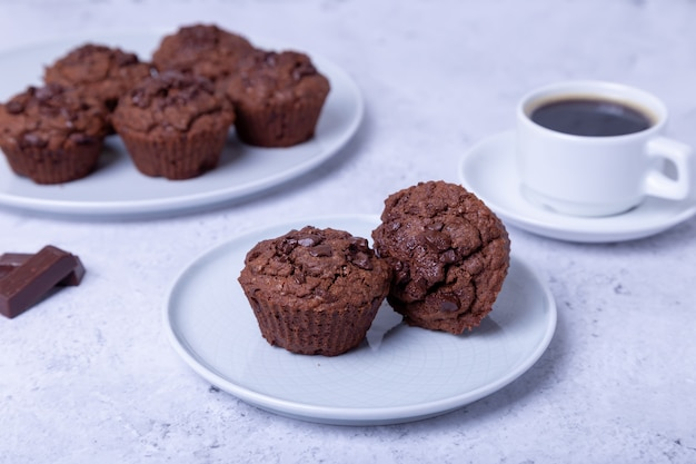 Chocolate muffins on a white plate. homemade baking. in the background is a cup of coffee. white background. selective focus, close up.