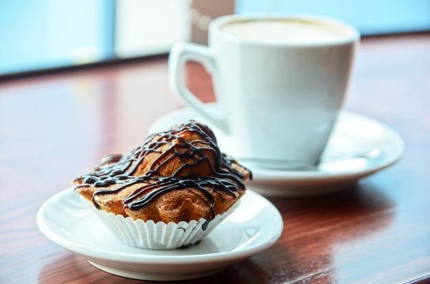 チョコレートのマフィンとオレンジ色のテーブルの上にコーヒーカップ