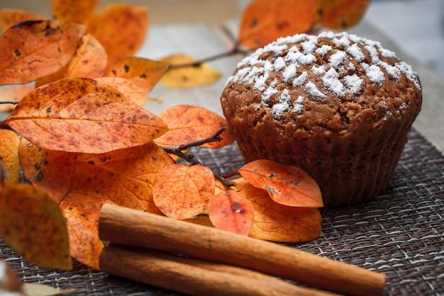 단풍과 계피를 배경으로 사과를 채운 초콜릿 머핀