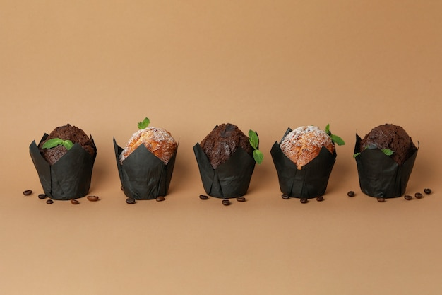 Chocolate muffins with coffee seeds on beige background.