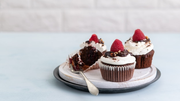 Chocolate muffins with a cup of coffee and fresh raspberries on the table, light banner,