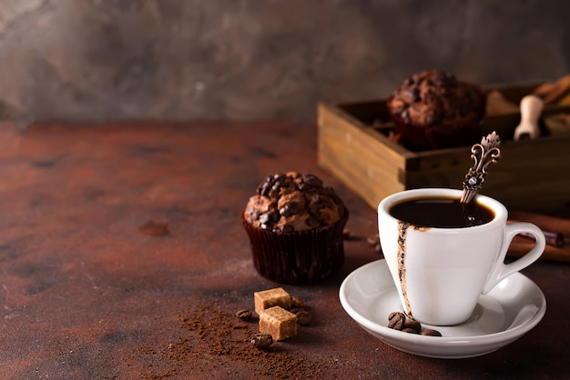 Chocolate muffins with cup of coffee on a wooden box with grains of coffee and spices