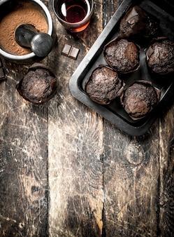 나무 테이블에 향기로운 차 초콜릿 머핀입니다.