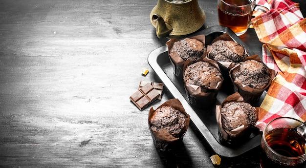 Chocolate muffins with fresh tea on black chalkboard.