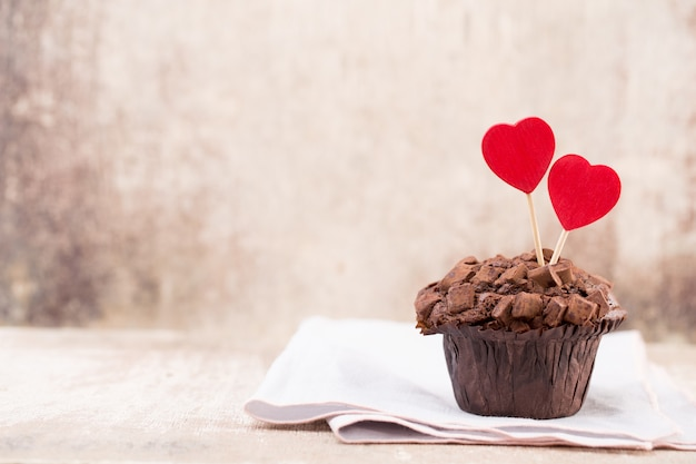 Chocolate muffins with heart on rustic wooden table
