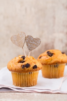 Chocolate muffins with heart vintage background, selective focus.