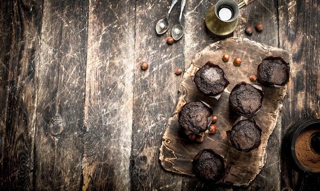 나무 테이블에 뜨거운 커피와 초콜릿 머핀입니다.