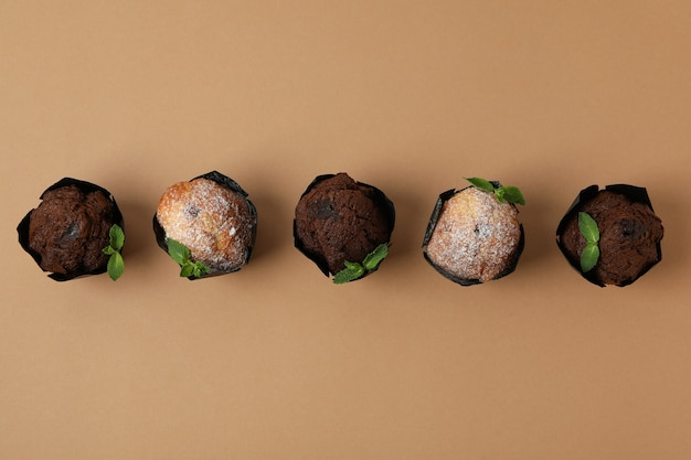 Chocolate muffins with mint on beige background.