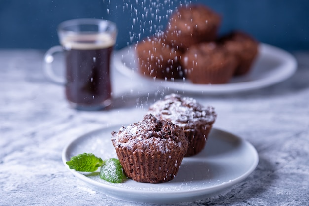 Chocolate muffins with mint on a black plate, strewed with icing sugar. homemade baking. in the background is a cup of coffee and a plate with muffins. marble table and blue background.