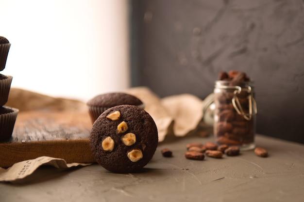 나무 테이블에 견과류와 초콜릿 머핀입니다. 맛있는 달콤한 디저트. 소박한 스타일.